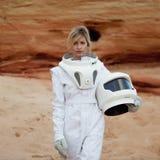 没有一件盔甲的未来派宇航员在另一个行星,与定调子的作用的图象 库存照片