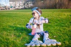 没有乳齿的逗人喜爱的卷曲女孩享受senjoys坐在溜冰鞋的草和太阳镜和开放瓶用水 库存图片