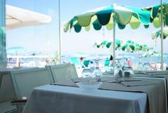 没有人,有有桌的地中海餐馆 从太阳的伞在绿色口气和海海滩是位于 免版税图库摄影