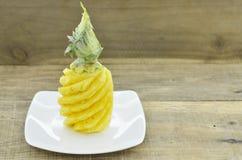 没有壳的菠萝在木桌上的白色板材 免版税库存图片