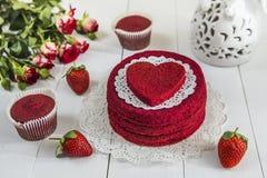 没有奶油色`红色天鹅绒`的红色蛋糕在一张白色木桌上,装饰用草莓、玫瑰和白色透雕细工花瓶有hea的 免版税库存图片