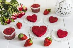 没有奶油色`红色天鹅绒`的红色蛋糕在一张白色木桌上,装饰用草莓、玫瑰和白色透雕细工花瓶有hea的 图库摄影