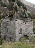 没有屋顶的腐烂的房子有在山的落的墙壁的 免版税图库摄影