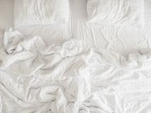 没有整理好的卧具板料和枕头,在舒适睡眠概念以后的没有整理好的杂乱床顶视图  库存图片