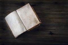 没有文本的老开放书在一张木桌上 库存图片