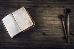 没有文本老木匙子的老开放书在一张木桌上 库存图片