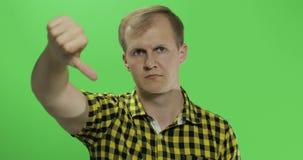 没有显示和给他的拇指的黄色衬衣的白种人年轻人下来 股票录像