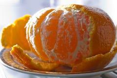 没有果皮的蜜桔在茶碟,点燃由太阳 免版税库存照片