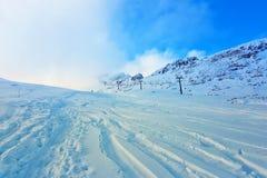 没有清除在积雪的山和随风飘飞的雪,滑雪倾斜中的空的滑雪吊车和没准备好游人 库存照片