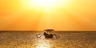 没有渔夫的渔夫小船巴厘岛的,在日落期间的印度尼西亚在海滩 免版税库存照片