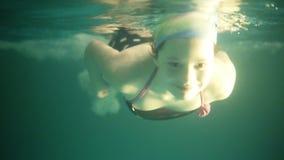 没有游泳风镜的微笑的女孩游泳在水面下在水池的 十几岁的女孩潜水的水中 上面英尺长度和 影视素材
