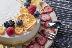 没有烘烤的饮食精美水果的莓果坚果蛋糕 在一张黑桌上的木立场 库存图片