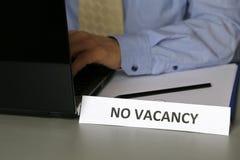 没有空位在蓝色衬衣的标志在办公室,坐在有膝上型计算机的书桌的商人和领带 免版税库存照片