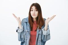 没有线索什么发生 被问的未察觉的可爱的女孩演播室画象有棕色头发的在时髦的牛仔布夹克 免版税库存照片