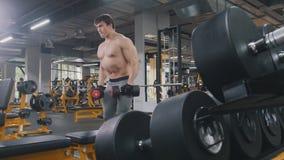 没有衬衣的运动员人举的哑铃在健身房 免版税图库摄影