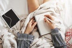 没有象床的地方 说谎在毯子,在耳机的听的音乐下的创造性和轻松的妇女通过数字式 免版税图库摄影