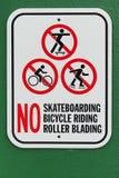 没有踩滑板的自行车骑马路辗叶栅标志有绿色背景 库存图片