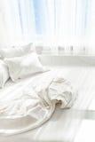 没有整理好的床照片反对窗口的 免版税库存照片