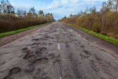 沥青农村路的危险坑洼 公路损伤 免版税库存图片