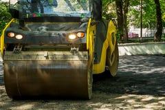 沥青夯捣式压路机在一个公园运转在一个晴朗的春日 柏油路修理  免版税图库摄影