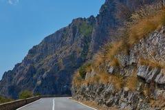 沥青详细形成路正方形人员结构 与美丽的山路的五颜六色的风景有完善的沥青的 高岩石,在日出的蓝天 免版税库存照片