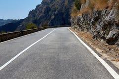 沥青详细形成路正方形人员结构 与美丽的山路的五颜六色的风景有完善的沥青的 高岩石,在日出的蓝天 库存照片