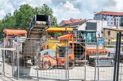 沥青路面工作的工业机械在街道建筑和重建站点包围与金属安全市分 免版税库存照片