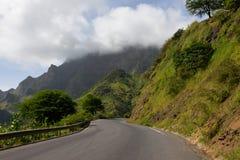沥青路,多云山背景,绿色倾斜风景,佛得角 库存照片