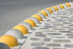 沥青鹅卵石分隔的遏制路 免版税库存照片