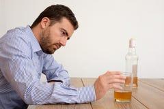 沮丧人滥用酒精设法忘记他的问题 库存照片