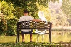 沮丧和哀伤的年轻人单独坐长凳在公园 免版税库存照片