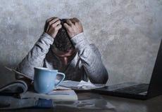 沮丧和被注重的年轻大学生人与课本笔记薄和便携式计算机书桌感觉一起使用在家淹没 免版税库存图片