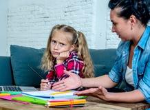 沮丧的一起做家庭作业的母亲和乏味女儿 免版税库存图片