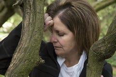 沮丧的中年妇女在倾斜在树的森林里 免版税图库摄影
