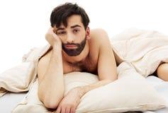 年轻沮丧的人在床上 免版税图库摄影