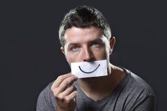 年轻沮丧的人在悲伤和哀痛丢失了对负纸与在他的嘴的面带笑容在消沉概念 免版税图库摄影