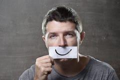 年轻沮丧的人在悲伤和哀痛丢失了对负纸与在他的嘴的面带笑容在消沉概念 免版税库存图片