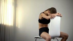 沮丧的厌食女孩坐椅子,用尽由营养不良,问题 库存照片