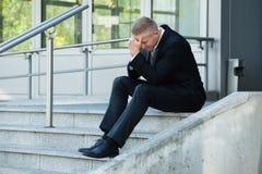 沮丧的商人坐台阶 图库摄影