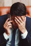 沮丧的商人谈话在电话 免版税库存照片