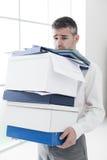 沮丧的商人运载的箱子 免版税库存照片