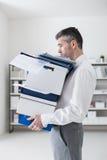 沮丧的商人运载的箱子 库存图片