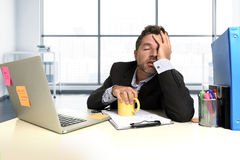 沮丧的在办公计算机书桌的商人绝望面孔表示痛苦重音 免版税库存照片