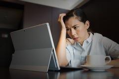 沮丧的女商人工作压力头疼弄翻与膝上型计算机在桌上 免版税图库摄影