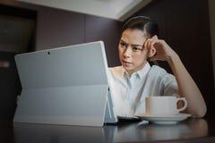 沮丧的女商人工作认为膝上型计算机的重音问题在桌上 库存图片