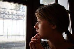 年轻沮丧的女孩是仔细考虑和看窗口 她是哀伤的 库存照片