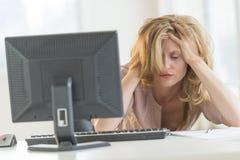 沮丧的女实业家用在坐在书桌的头发的手 库存图片
