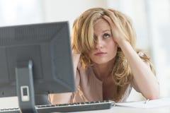 沮丧的女实业家用在头发的手在办公桌 免版税库存照片