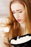 年轻沮丧的妇女吃着大碗冰淇凌对comfor 免版税库存照片