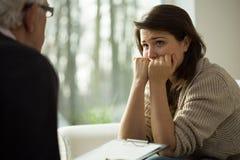 沮丧的妇女听她的治疗师 库存照片